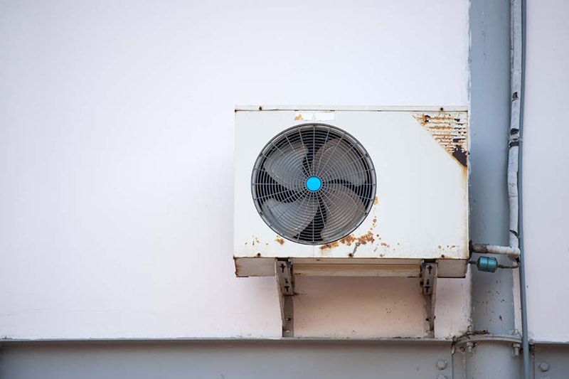 A rusted air conditioner mounted in a wall | Signs AC Repair Replace | 3 Telltale Signs It's Time for a New AC | Farmington Hills, MI