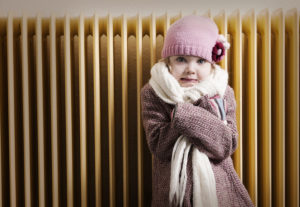 Cold girl in front of a heater.