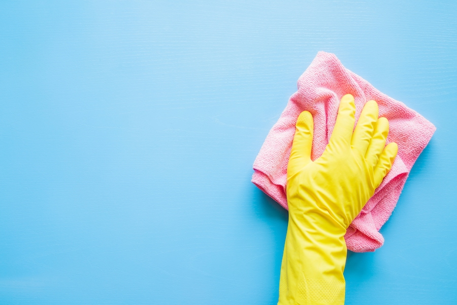 Yellow gloved hand washing blue wall.